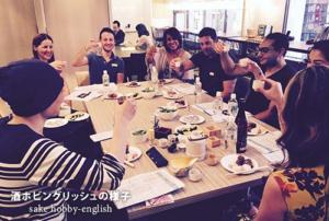 外国人と日本人が同じ机で日本酒で乾杯している